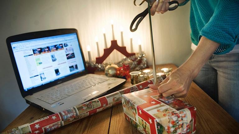 En person slår in julklappar bredvid en bärbar dator. Foto: Mikael Andersson/TT.