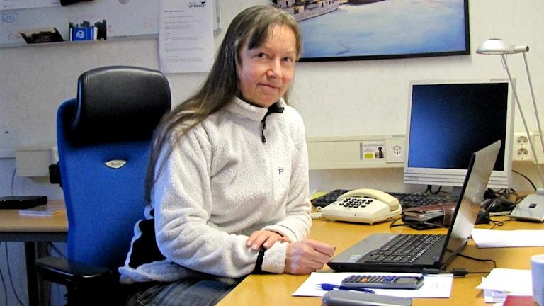 Merit Nerstrand sitter vid skrivbordet på kontoret. Det är där hon får betala sina räkningar eftersom internet fortfarande inte fungerar efter stromen Egon.