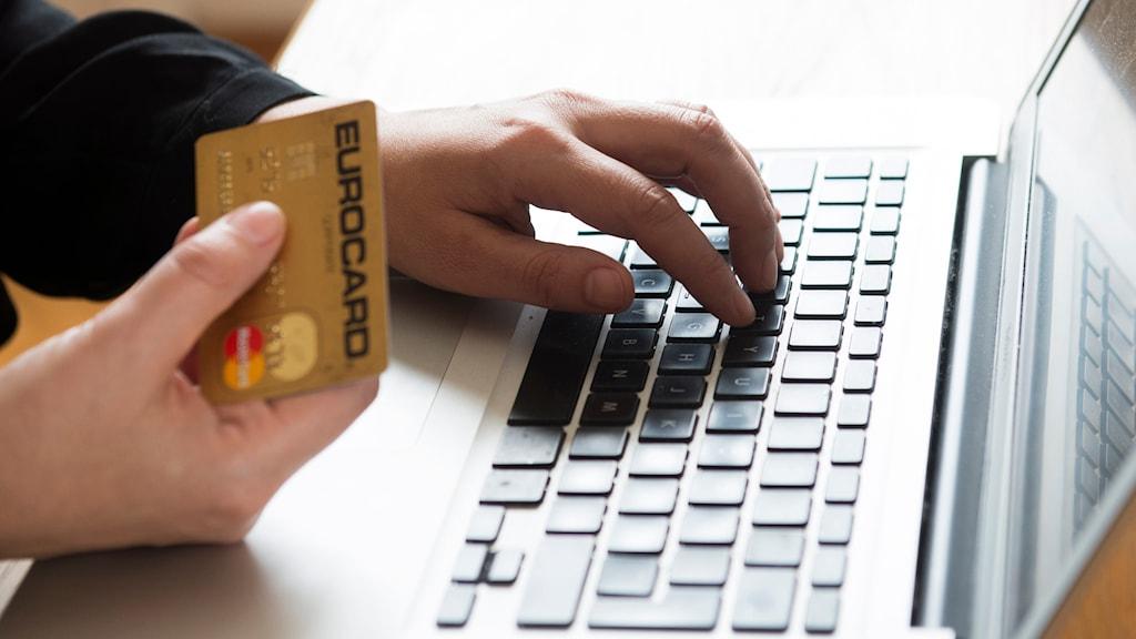 En man håller i ett kreditkort och skriver samtidigt på en laptop. Foto: Fredrik Sandberg/TT.