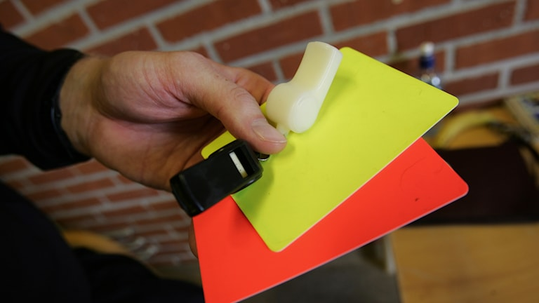 En man håller i ett gult kort, ett rött kort och en visselpipa. Foto: Fredrik Sandberg/TT.
