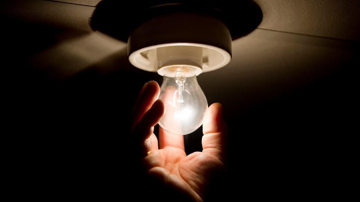 En person skruva i en glödlampa. Foto: Jessica Gow/TT.