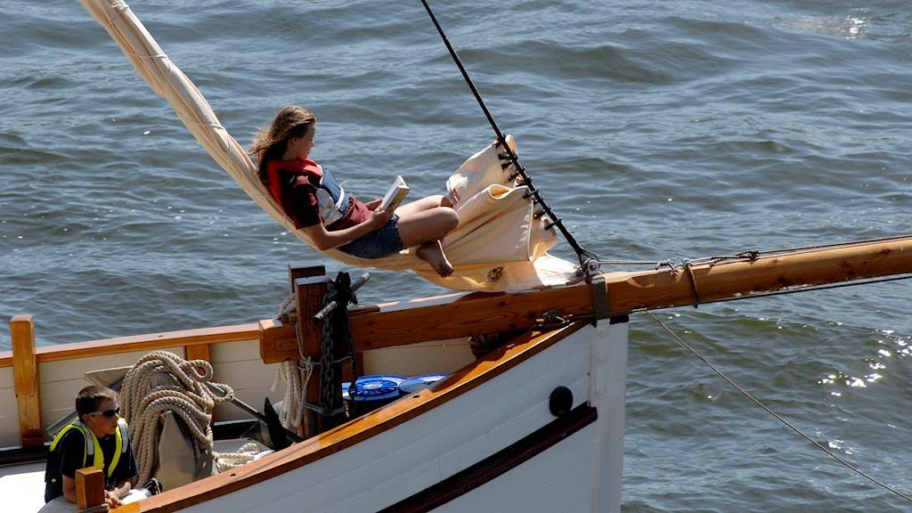 Flicka sitter på båt och läser bok i solen. Foto: Hasse Holmberg/TT