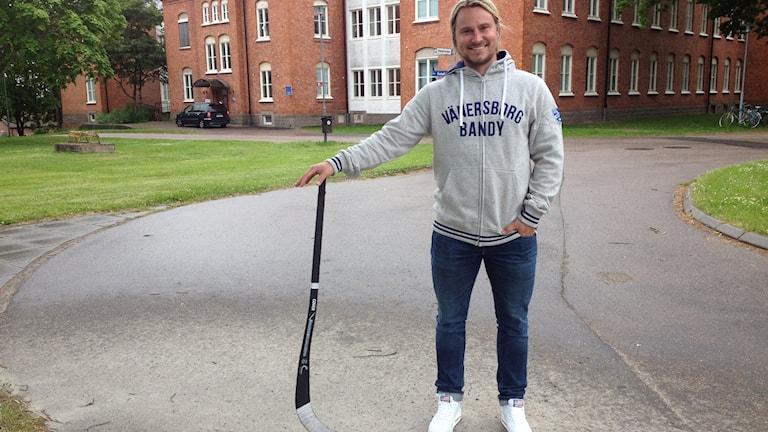 En man stor framför en byggnad med en bandyklubba i handen. Foto: Lina Alexandersson/Sveriges Radio
