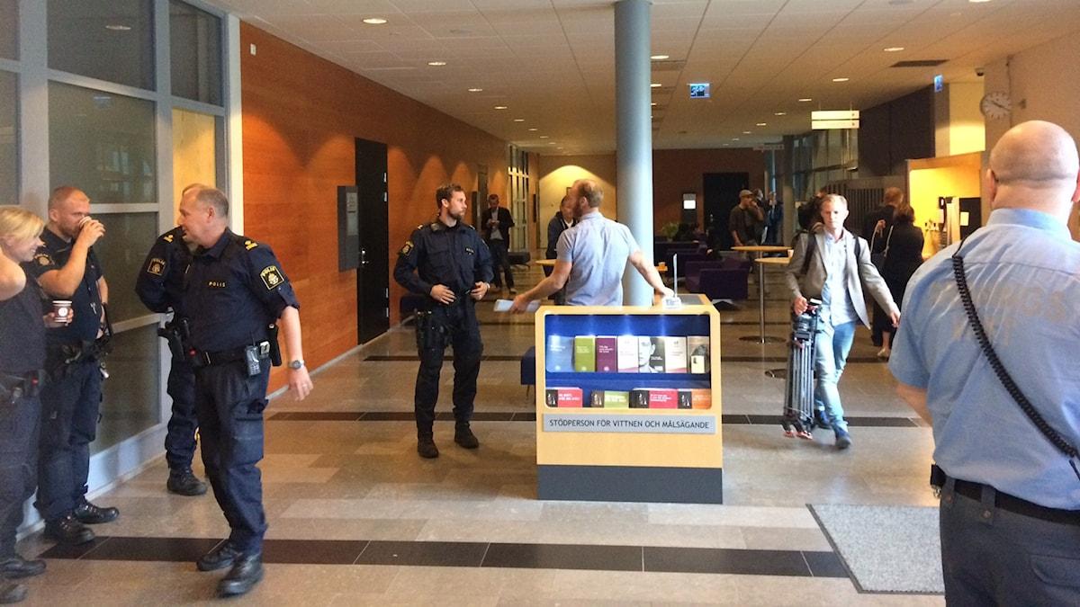 Poliser och andra personer utanför tingssalarna i Göteborg. Foto: Victor Jensen/Sveriges Radio.