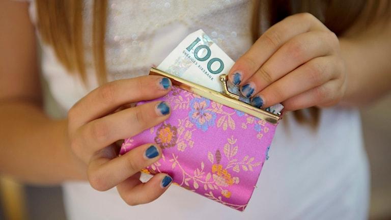 En flicka stoppar ner sin veckopeng i en plånbok. Foto: Henrik Montgomery/TT.