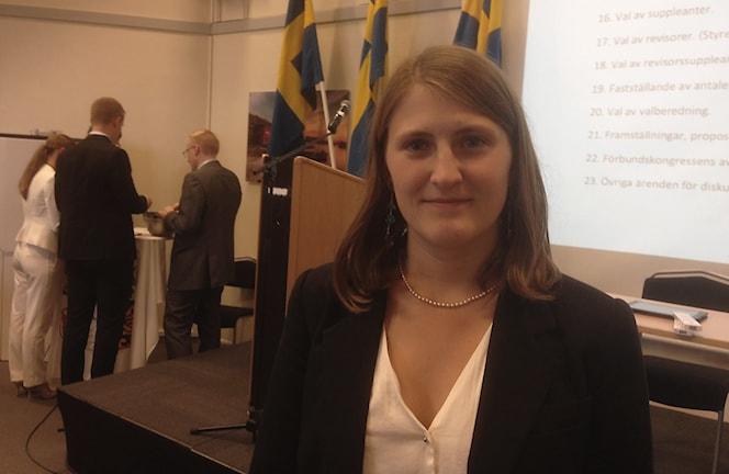 Jessica Ohlson står framför podiet, bakom sig har hon några svenska flaggor och en skärm där man kan läsa dagens schema för kongressen. Hon ler och tittar in i kameran. Foto: Elisabeth Cederblad/P4 Väst