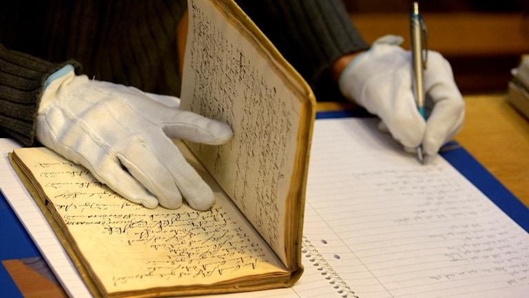 En släktforskare på Riksarkivet. De gamla böckerna på Riksarkivet måste hanteras varsamt med mjuka handskar för att inte slitas eller gå sönder. Foto: Janerik Henriksson/TT.