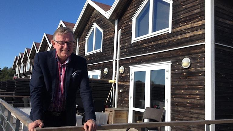 En man står utanför en länga med sjöboar. Foto: Margareta Waldermarsdotter/Sveriges Radio