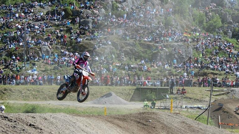 En motocrossförare flyger över ett hopp. Foto: Tomas Bader/Sveriges Radio.