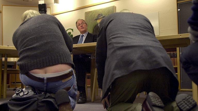 Bild på Fotografer som sitter på knä och fotograferar Lennart Daléus (c). De ses bakifrån. Den ene har en glipa mellan byxor och tröja så att kalsong-linningen och svanskotan syns. Foto: Mark Earthy/TT Bild