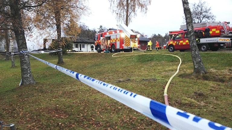 Polisen avspärrning och barndbilar vid eldhärjat asylboende i Munkedal. Foto: Margaretha Valdemarsdotter/Sveriges Radio.