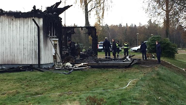 Polisens personal tillsammans med polishund i det nedbrända huset vid asylboendet i Munkedal. Foto: Victor Jensen/Sveriges Radio