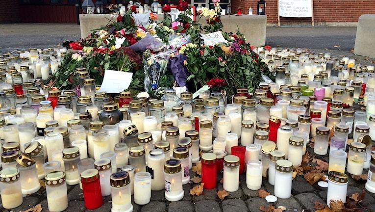 Ett stort antal gravljus och mängder med blommor utplacerade till minne av offren i knivattacken i Trollhättan. Foto: Victor Jensen/Sveriges Radio