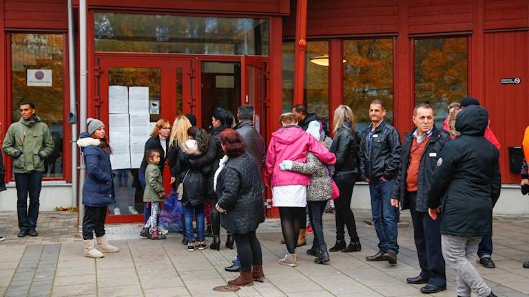 Människor väntar utanför ingången till skolan Kronan i Trollhättan. Foto: Thomas Johansson/TT