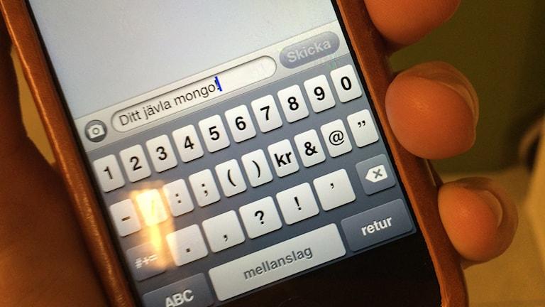 En elak sms-text på en mobiltelefon. Foto: Susanne Nobel/Sveriges Radio
