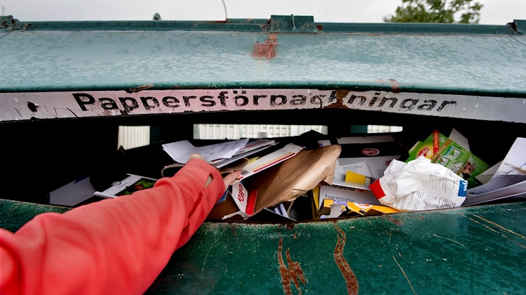 En kvinna slänger papperförpackningar i källsorteringscontainern. Foto: Pontus Lundahl/SCANPIX