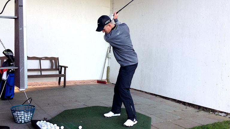 Marcus Kinhult måttar ett slag med golfklubban på Skaftö GK. Foto: Lasse Sergård/Sveriges Radio