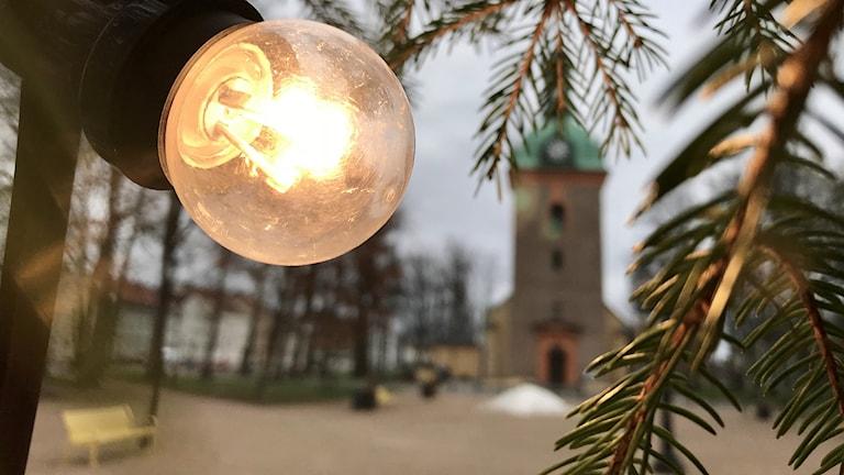 En bild på planen framför kyrkan i Vänersborg. Granris och granljus i förgrunden.
