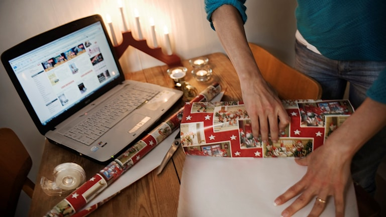 En kvinna stoppar ner en julklapp i en påse. Foto: Mikael Andersson/TT.