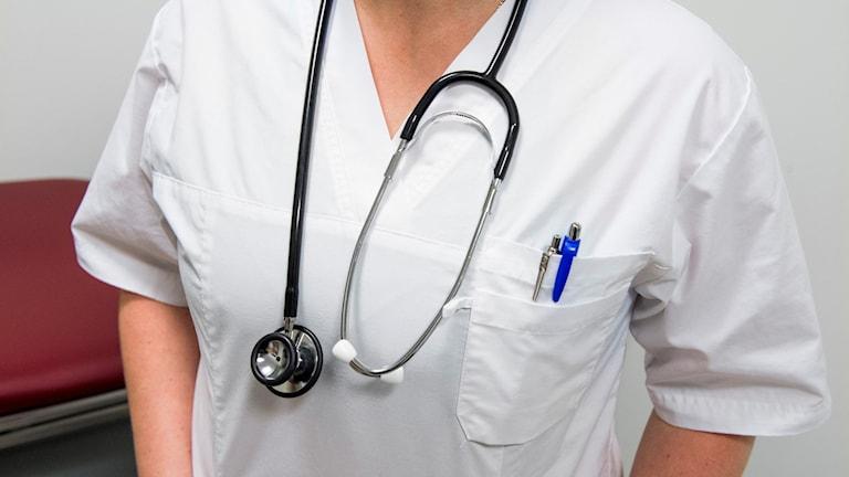 En kvinna som bär vit, kortärmad arbteströja och ett stetoskop runt halsen. Snart ska hemtjänspersonalen få samma kläder som finns inom sjukvåden. Foto: Claudio Bresciani/TT