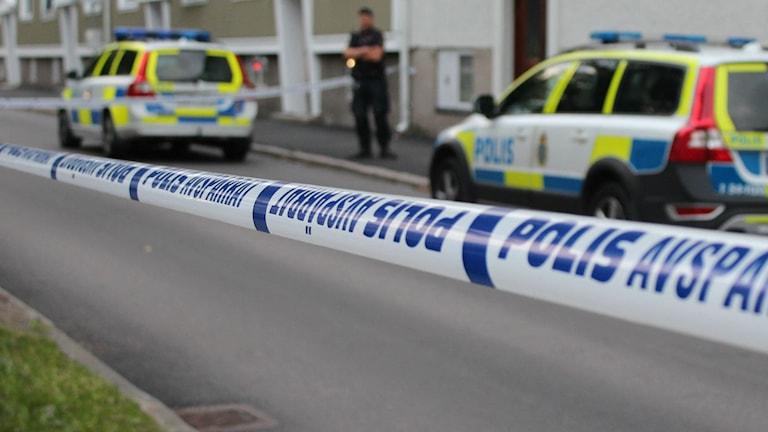 En polisman och två polisbilar framför ett lägenhetshus. Platsen är avspärrad med polisens plastband. Foto: Tommy Öster/Sveriges Radio.