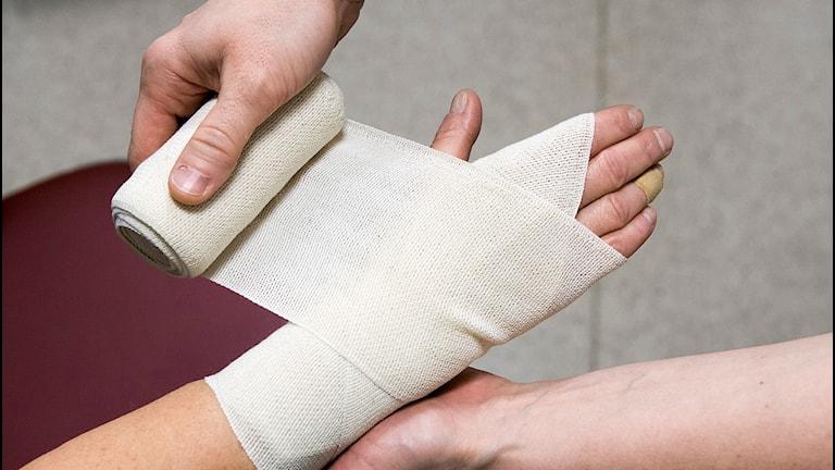 Sjuksköterska lägger bandage på hand och handled. Foto: Claudio Bresciani / TT