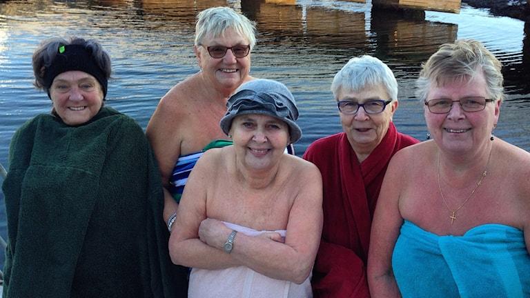 Vinterbadarna i bara handduk framför det iskalla vattnet. Från vänster till höger: Britta Söderlund, Eva Lysell, Hjördis Nilsson, Inga-Lena Carlsson och Anita Gustafsson. Foto: Joel Hansson/Sveriges Radio.