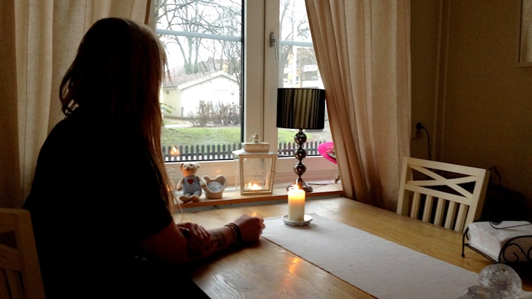Systern till det kvinnliga offret i trippelmordet i Uddevalla. Hon sitter bortvänd från kameran vid ett köksbord. Foto: Margaretha Valdemarsdotter/Sveriges Radio.