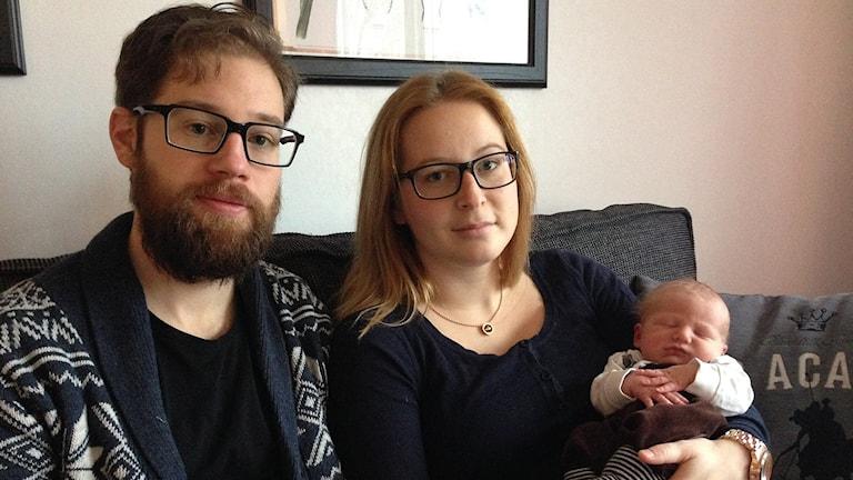 Niklas och Jenny Kjellsson i Brastad med en liten nyfödd bebis i famnen. Foto: Max Lindahl/Sveriges Radio.