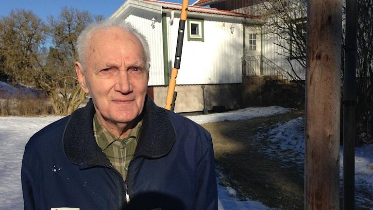 88-årige Bengt Zakrisson bredvid en telefonstolpe utanför hans hus.