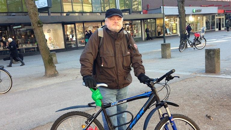 Anders Vallström med sin cykel på en gata i centrala Trollhättan.