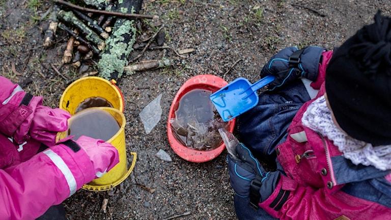 Barn leker utomhus med spade och hinkar.