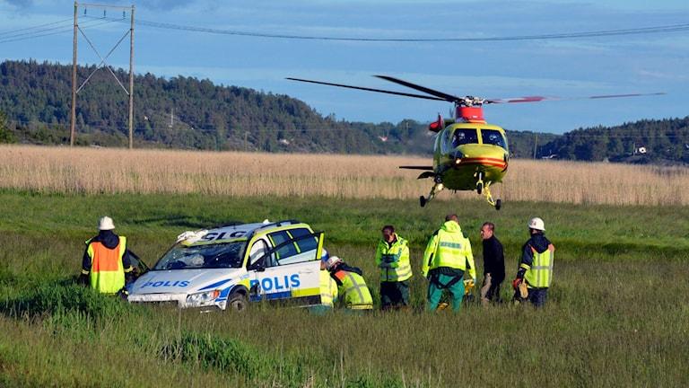 Polisbil på ett fält, omringad av räddningspersonal. En ambulanshelikopter hovrar bakom. Foto: Mikael Berglund/Nyheter STO.