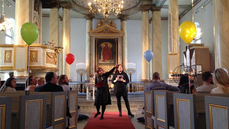 Det är en bild tagen inuti Vänersborgs kyrka, det står två kvinnliga präster längst fram och altargången är kantad med färgglada ballonger
