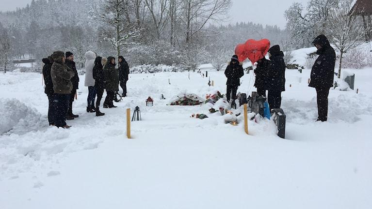 Anhöriga som samlats vid gravar på en begravnignsplats.