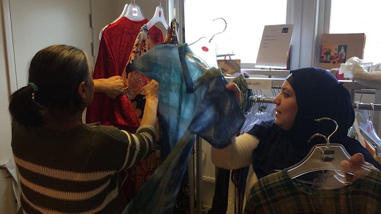 Ordföranden Salima Daidan och praktikanten Florije Maliqi på mötesplatsen Kvinnokoden visar några av de klädesplagg Florije hunnit göra.