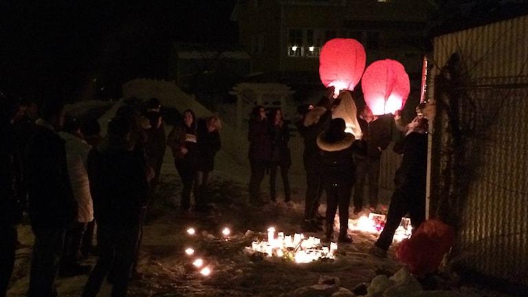 Ett flertal sörjande samlas för att släppa upp röd och vita svävande ljuslyktor mot himlen. Tända ljus och blommor syns på marken.