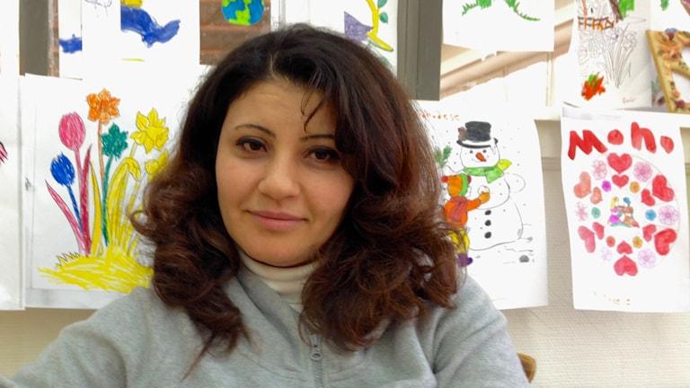 Den syriska kvinnliga hudläkaren Maha Aljundi framför barnteckningar.