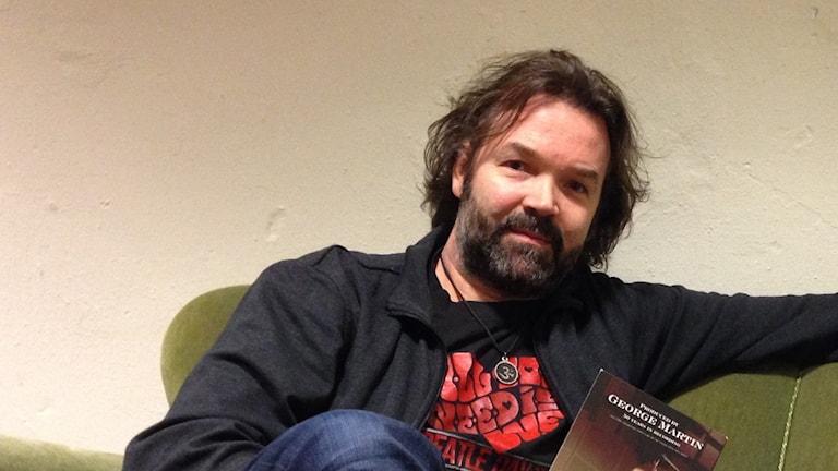 En man med längre mörkt hår sitter i en grön sammetssoffa med en bok om Beatlesproducenten George Martin i handen