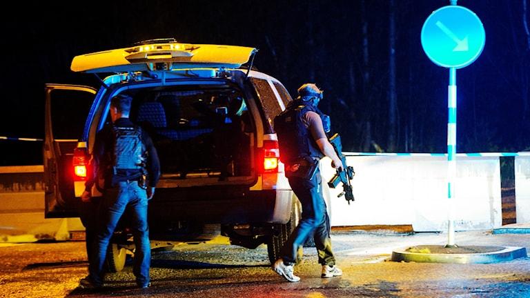 Polisens insatsstyrka med automatvapen vid en bilbrand i Sköndal.