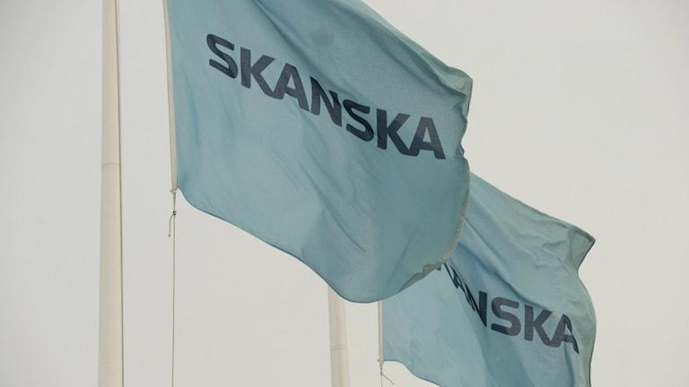 Två gråblå Skanskaflaggor vajar i vinden.