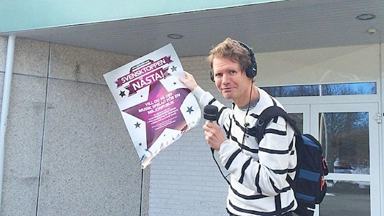 Peter Olsson med en affisch om Svensktoppen nästa.