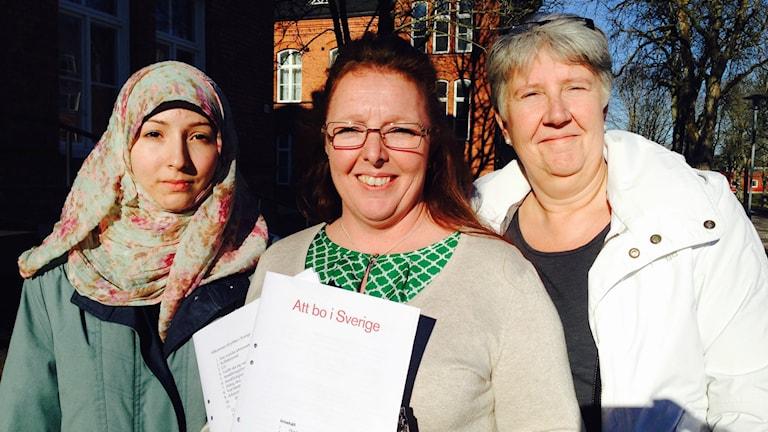 Tre kvinnor står utanför asylboendet Restad gård. Till vänster Ehaa Dagstani, iklädd slöja, asylsökande och testläsare. I mitten en leende Helena Löhman, ABF. Till höger Maria Hjelm, hyresgästföreningen.