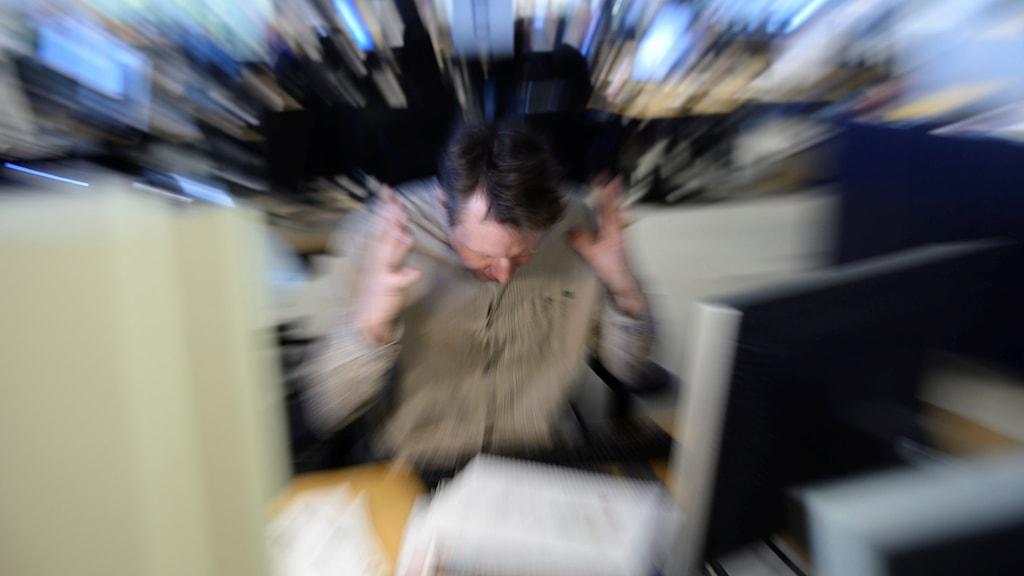 En man sitter vid en dator och tar sig över tinningarna.