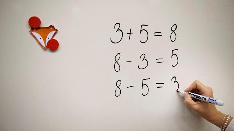 En person skriver mattetal på tavlan.