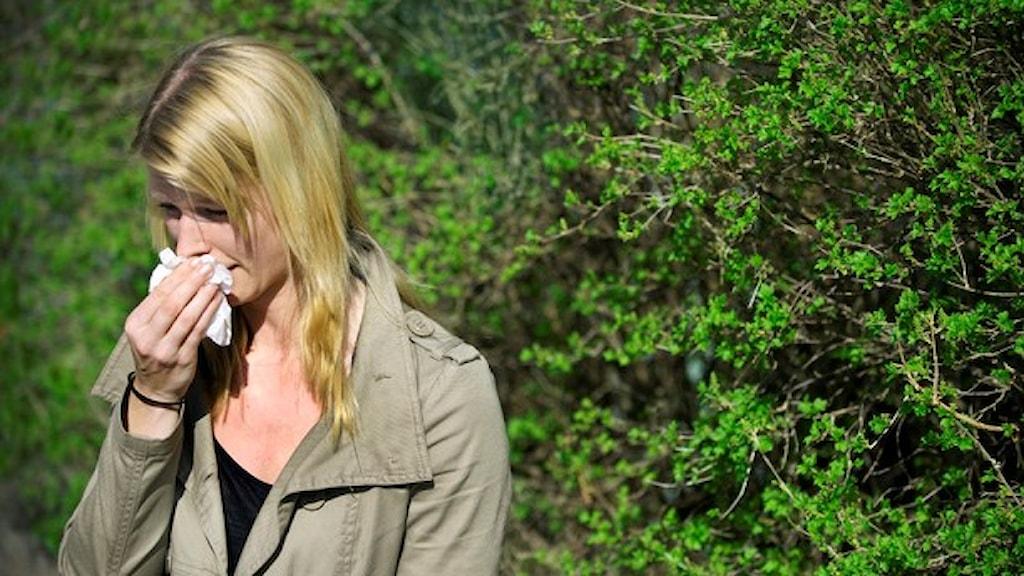 En kvinna med en näsduk vid näsan.