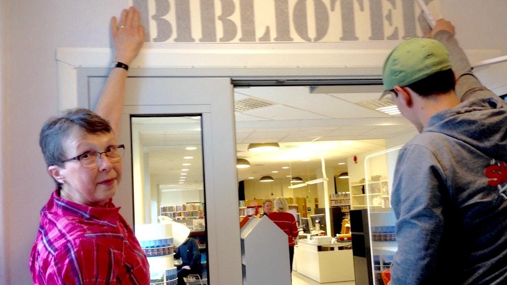 Bibliotekarien Ellan Johansson övervakar uppsättningen av nya bibliotelsskylten.