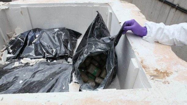 En person lyfter upp en påse med narkotika som gömts i ett kalkblock.