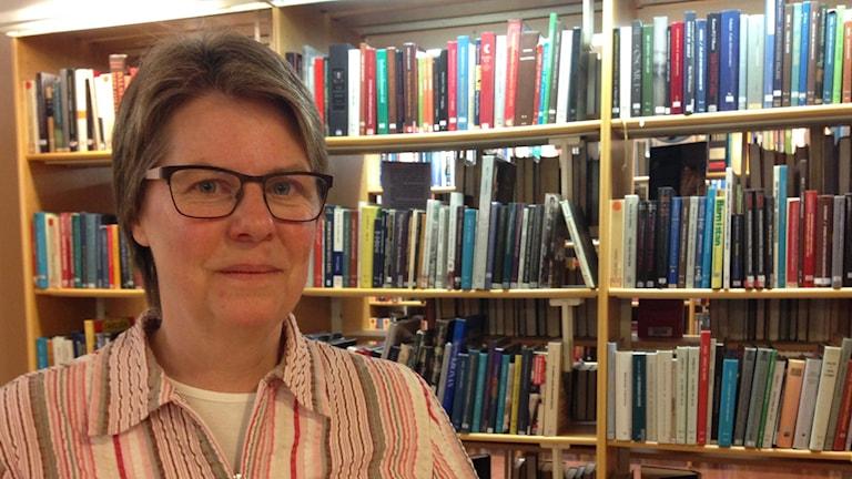 Medelålderskvinna med glasögon i randig skjorta står framför bokhylla fylld med böcker