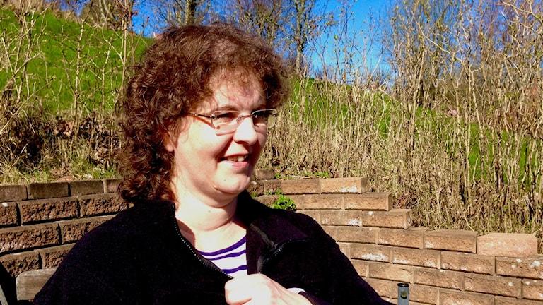 Monica Hansson i solen utanför sin bostad.